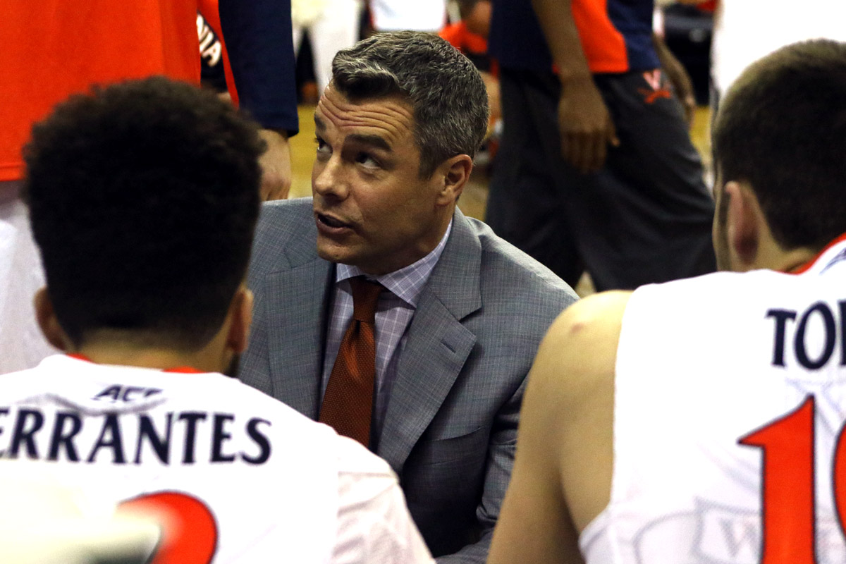 Tony Bennett talks to his Virginia basketball players in a huddle.